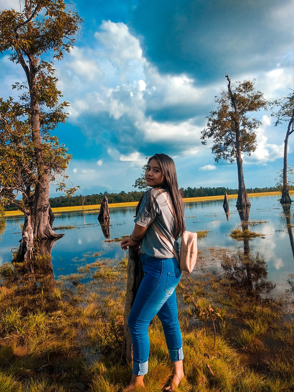woman in blue denim jeans standing near body of water during daytime