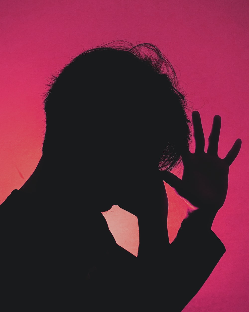 silhouette of person covering face with hands