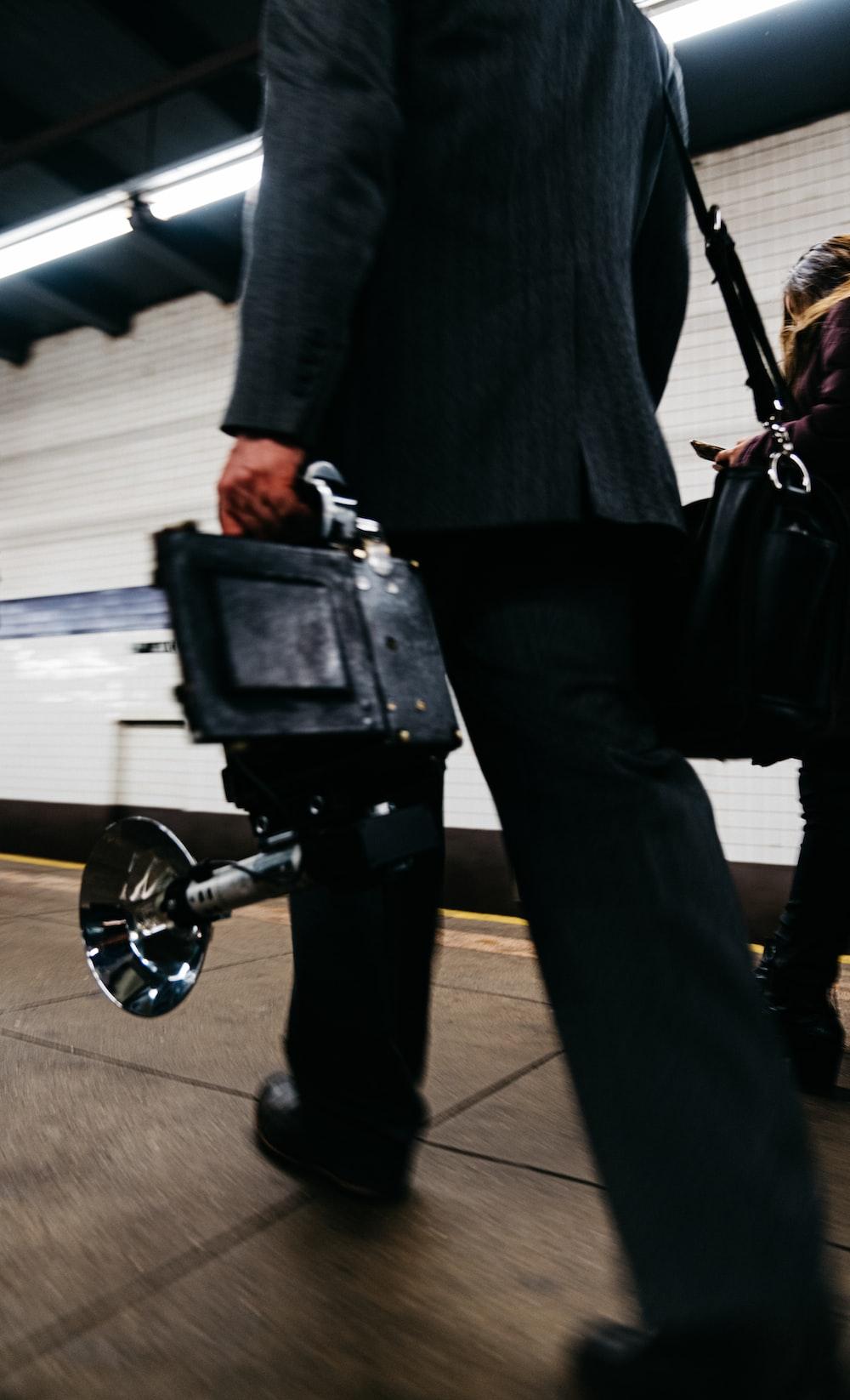 man in black suit jacket and black pants standing beside black wheel chair