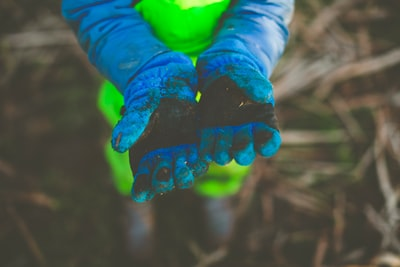 Boy at natural outdoor experience adventure with mudpants and dirty gloves