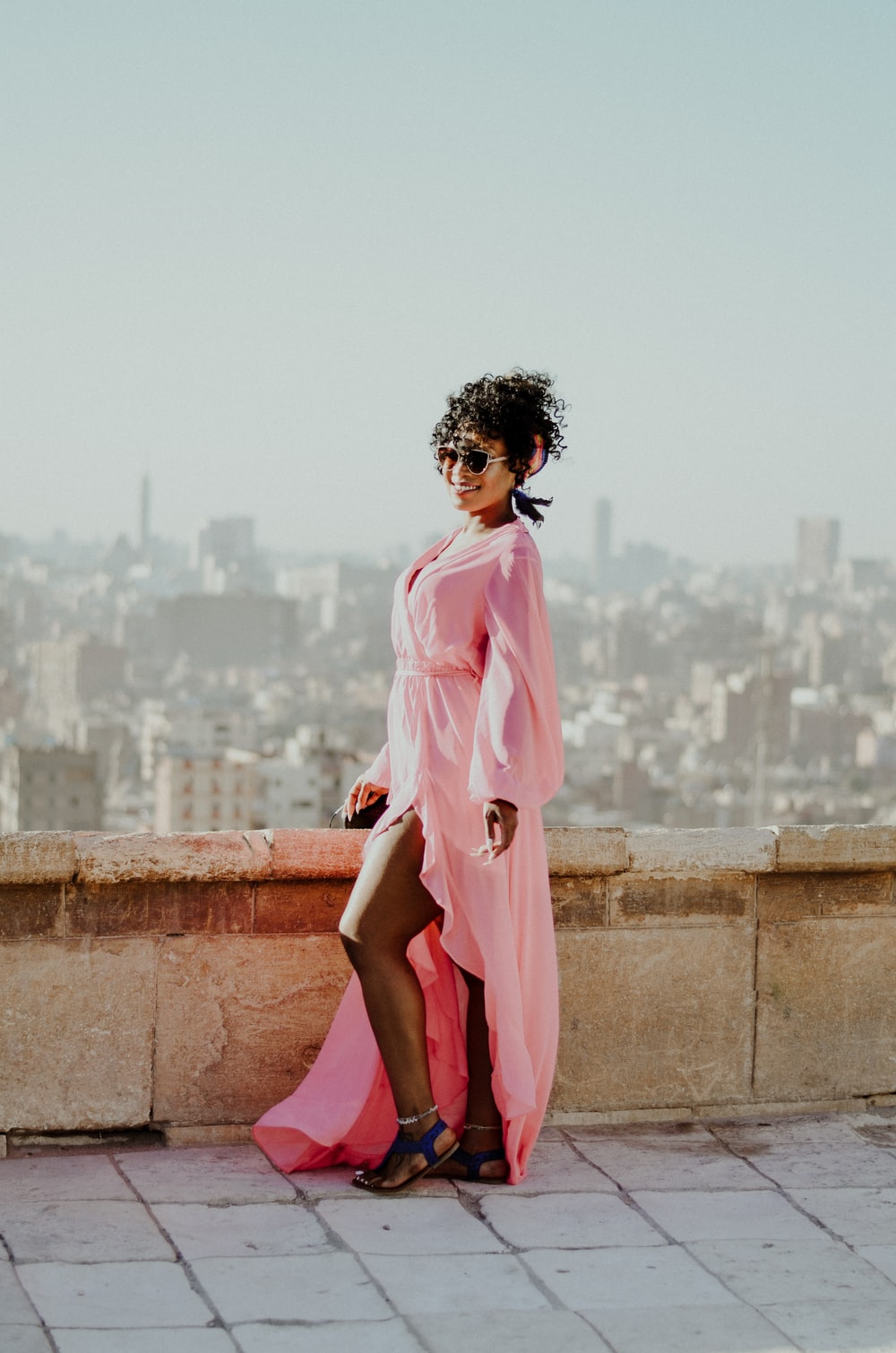 woman in pink dress standing on brown concrete wall during daytime