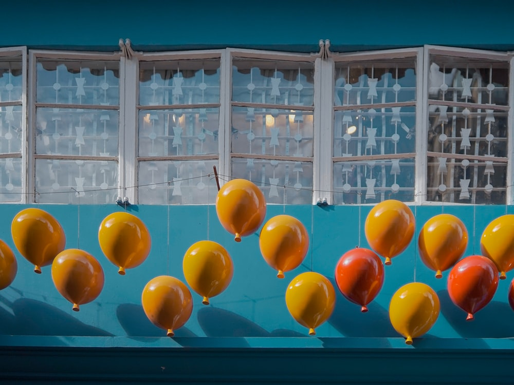 yellow red and blue balloons on white metal frame glass window