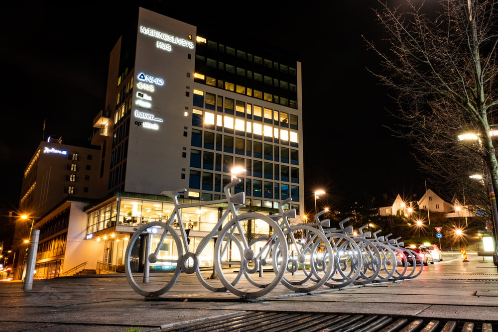 bicycles parked on a parking lot near a building during night time