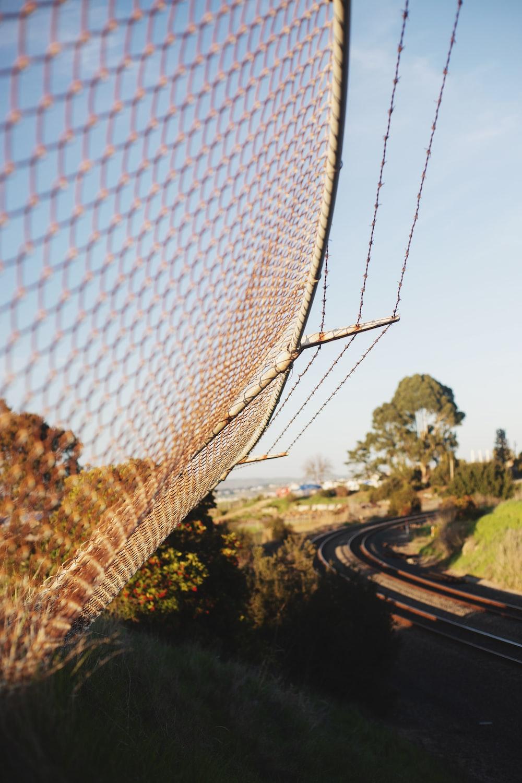 white net near green trees during daytime
