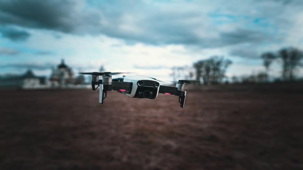 white and black drone flying in mid air during daytime