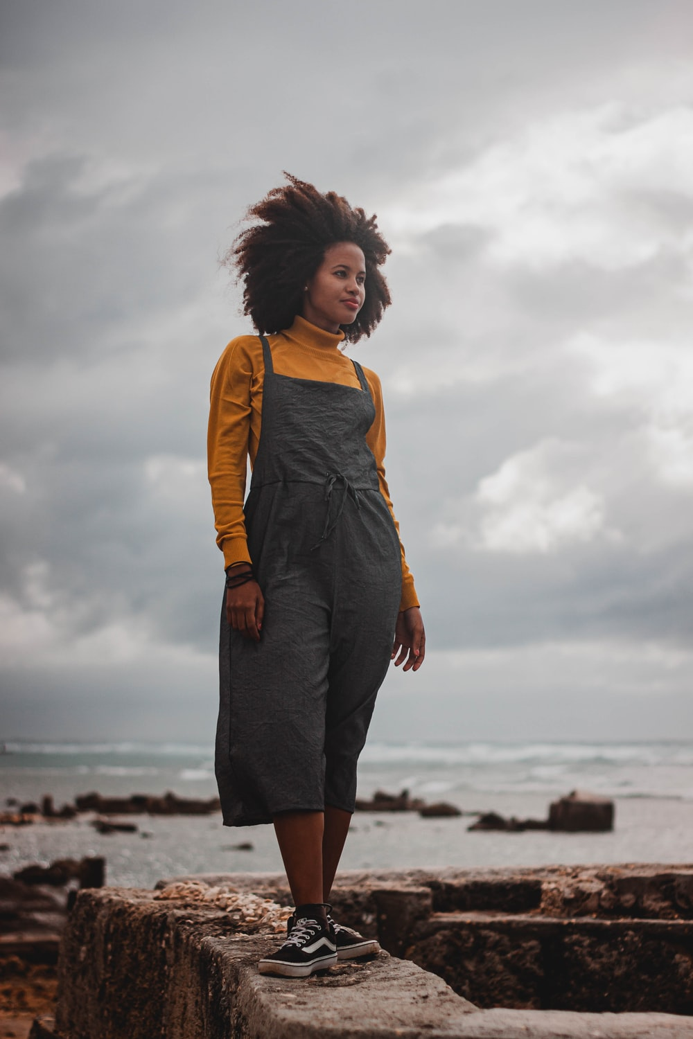 woman in yellow shirt and black skirt standing on beach during daytime