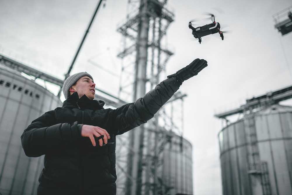 man in black jacket and black pants holding black and white drone