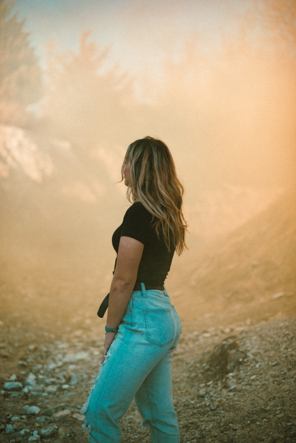 woman in black shirt and blue denim shorts standing on brown field