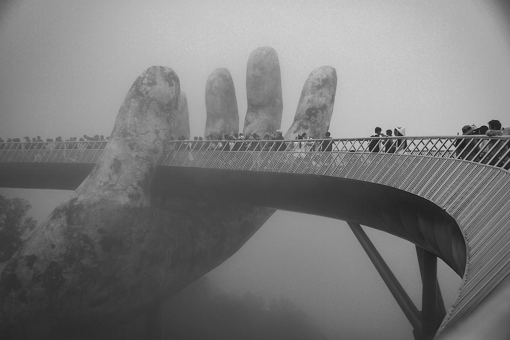 grayscale photo of man standing on bridge