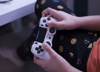 person holding white sony ps 4 controller