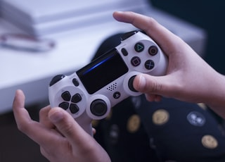 person holding white and black game controller
