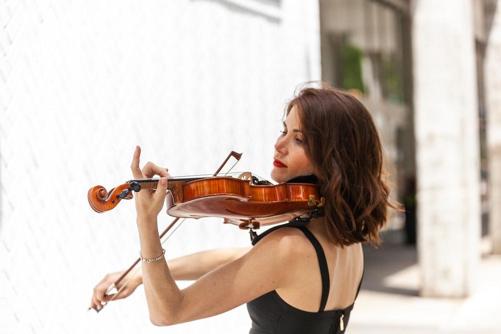 バイオリンを弾いて黒のタンクトップの女性