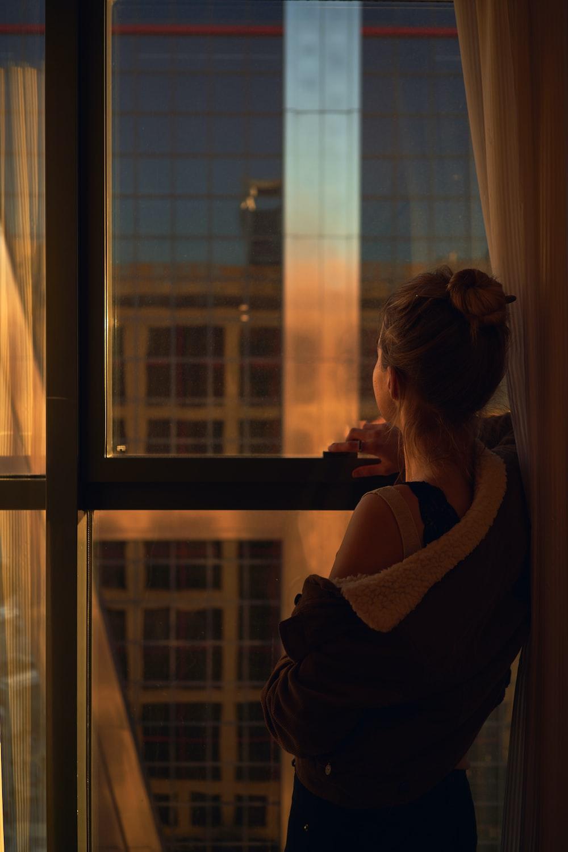 woman in black sweater standing beside glass window