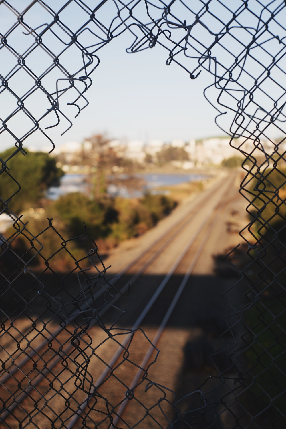 brown field with gray chain link fence during daytime