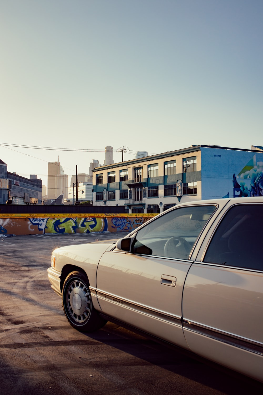 white sedan parked near blue building during daytime