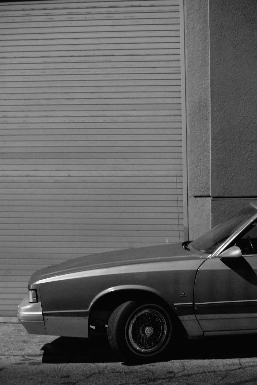 grayscale photo of car near wall