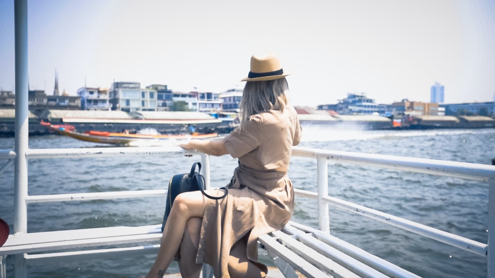 woman in brown dress sitting on brown wooden bench during daytime