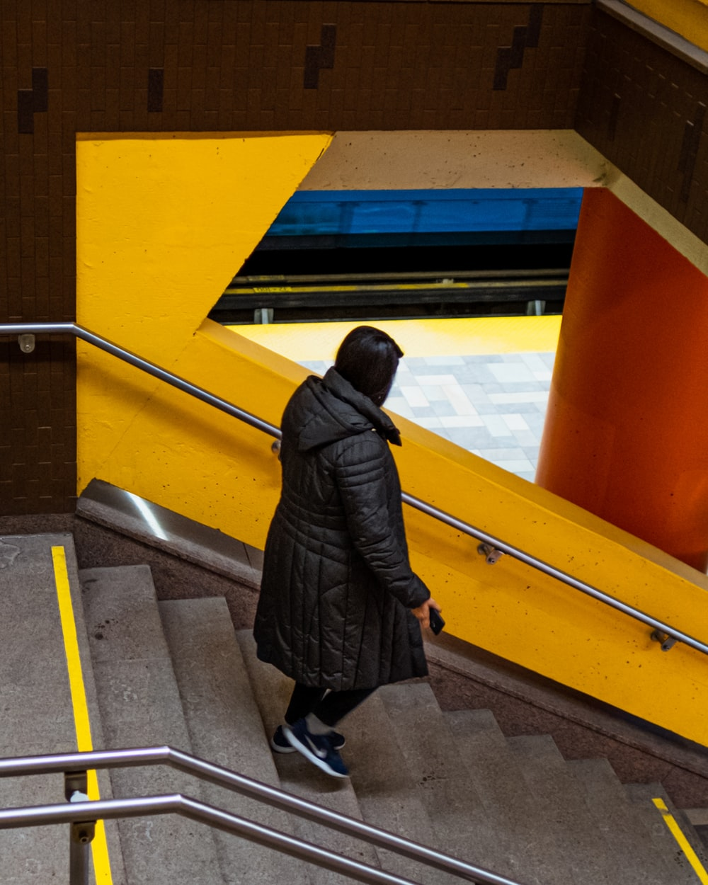 woman in black coat walking on yellow and gray staircase
