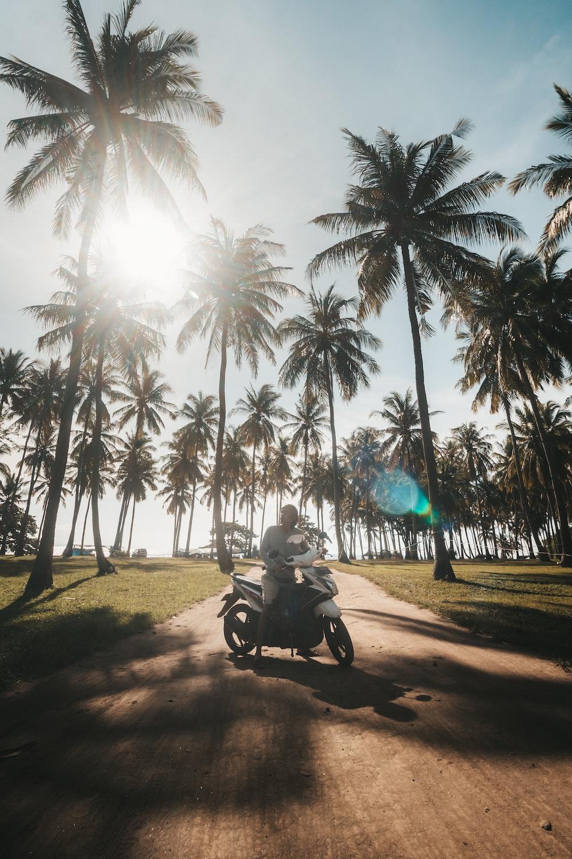 man in black shirt riding motorcycle on road during daytime