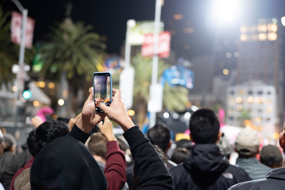 man in red jacket holding iphone taking photo of people during nighttime