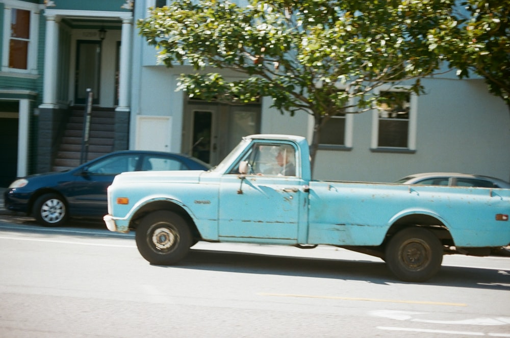 blue and white single cab pickup truck parked near green tree during daytime