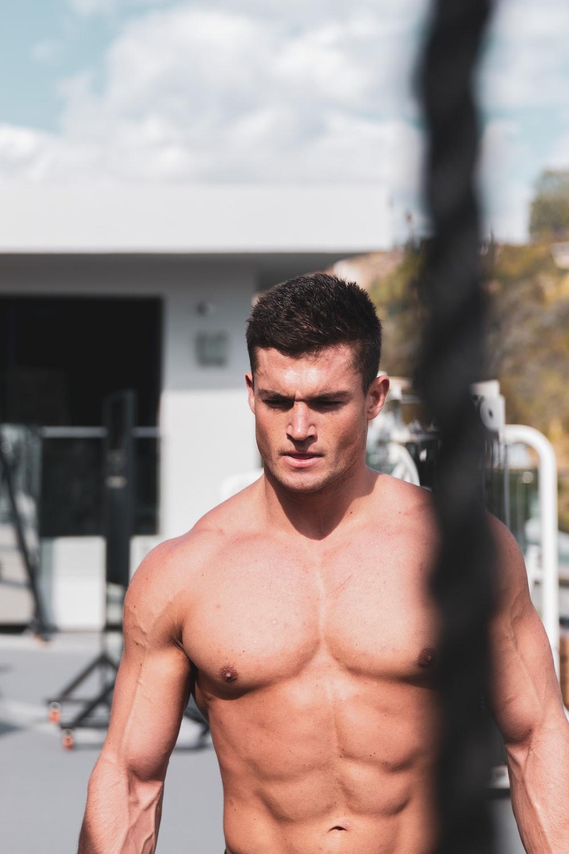 topless man standing near white metal railings during daytime