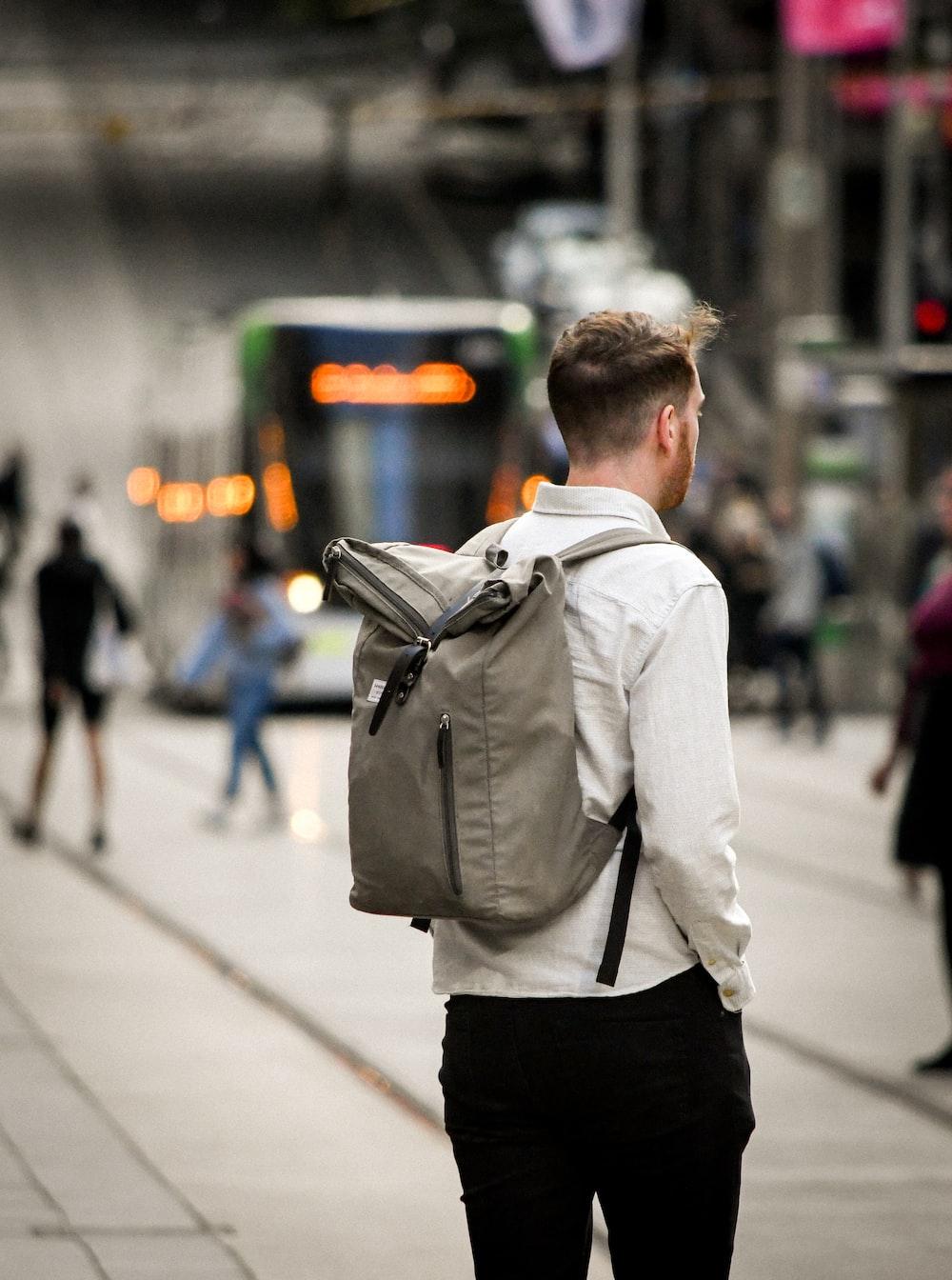 man in white dress shirt and black pants carrying black backpack walking on sidewalk during daytime