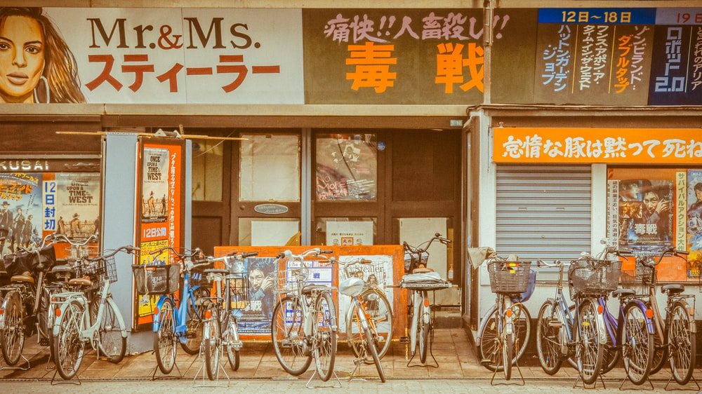 blue city bike parked beside brown wooden table
