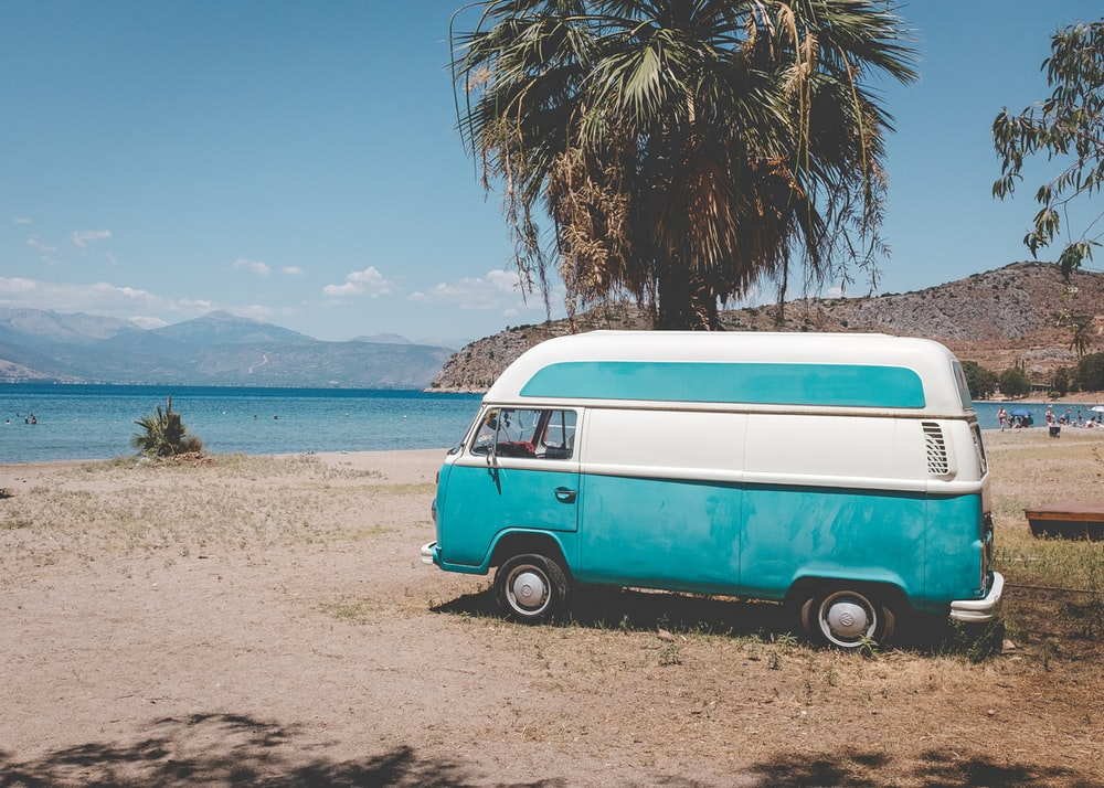 blue and white volkswagen t-2 parked on beach shore during daytime