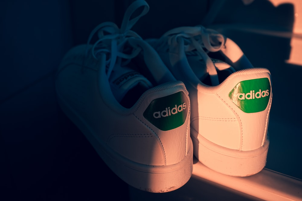 white adidas low top sneakers
