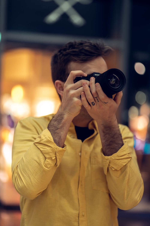 man in yellow dress shirt holding black camera