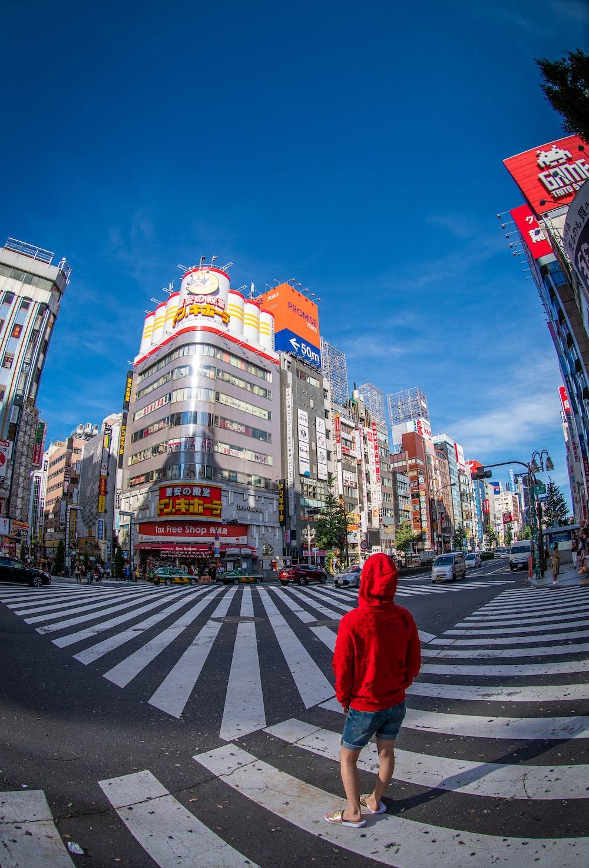 person in red hoodie walking on pedestrian lane during daytime