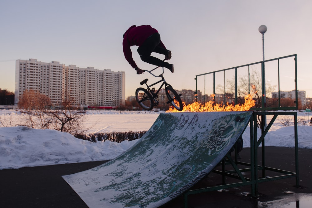 man in black jacket and pants riding on black bicycle on snow covered ground during daytime