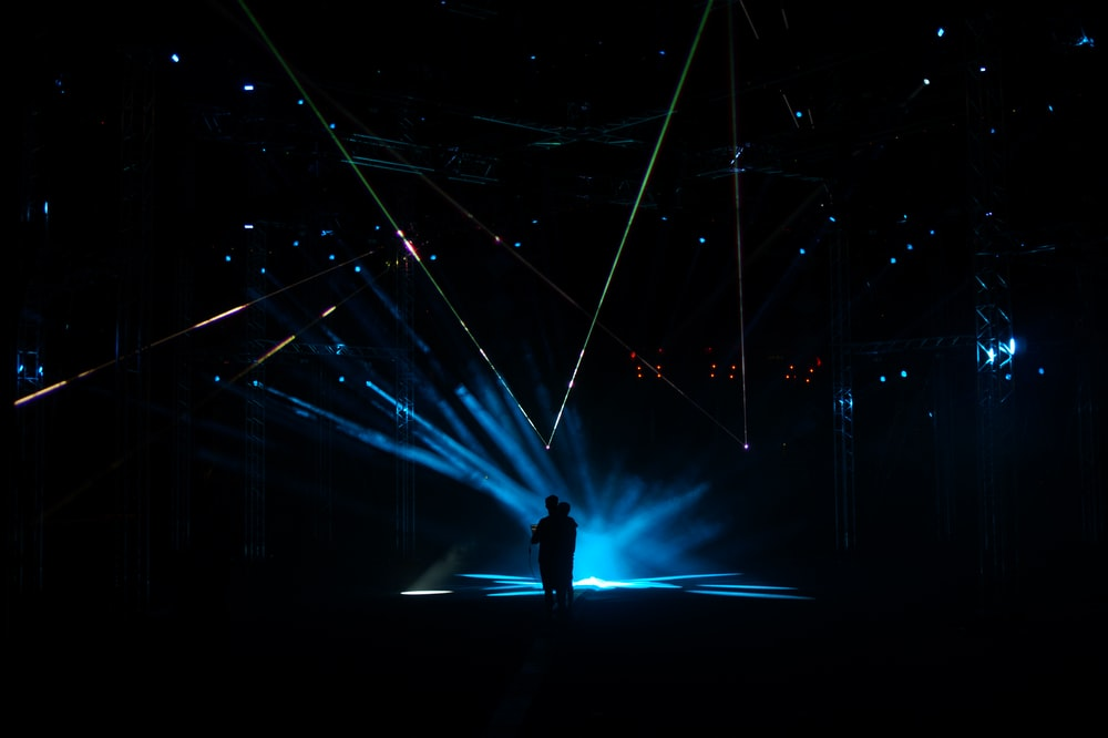 man standing on stage with lights