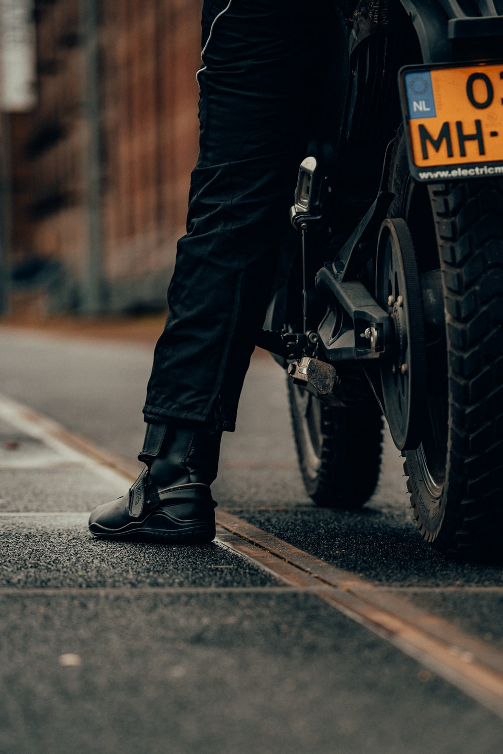 person in black leather boots riding motorcycle on road during daytime