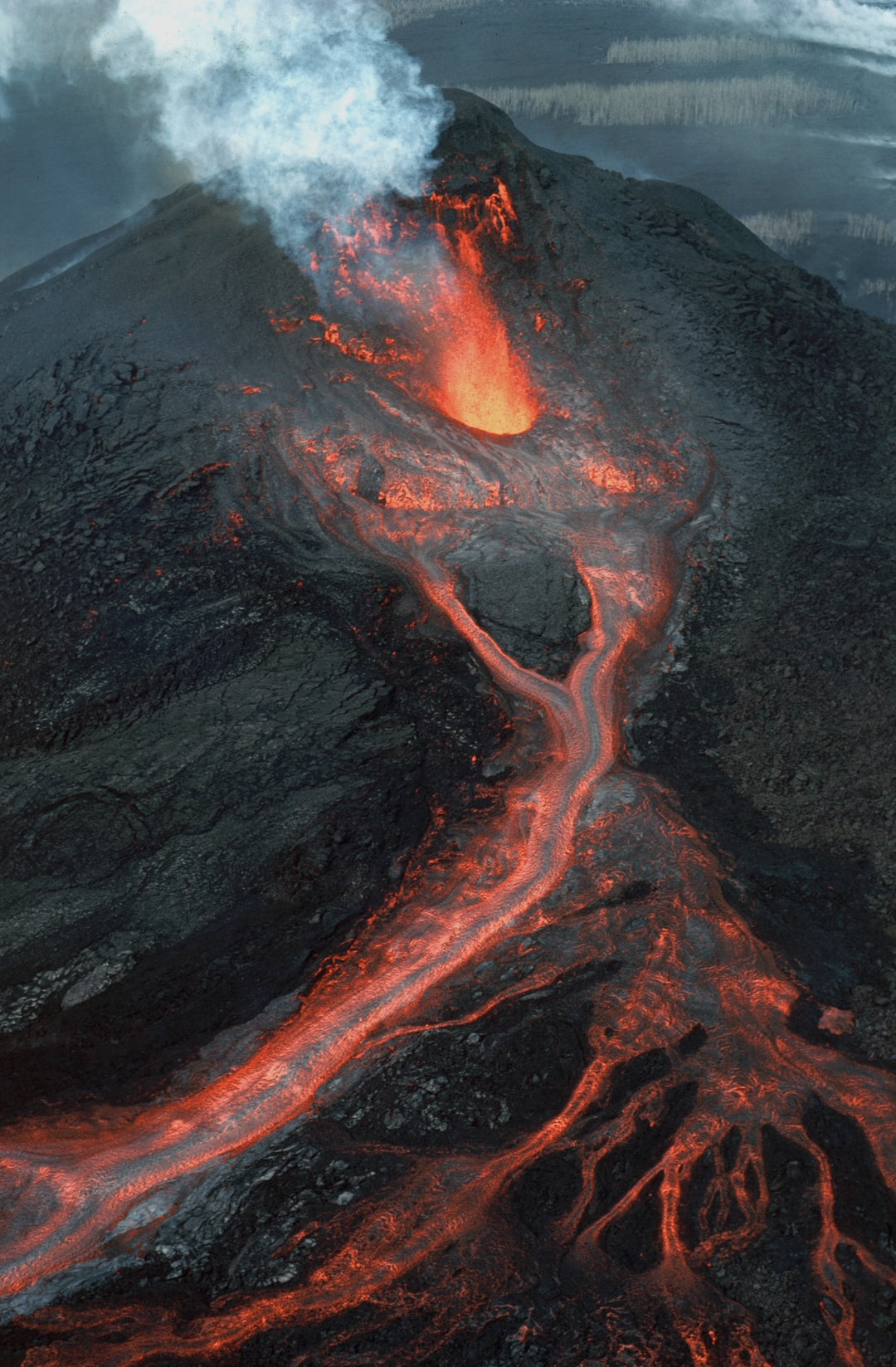 Aerial view, from the east, of waning lava fountain from Pu'u 'O'o on Hawai'i Island's Kilauea Volcano. Taken at the end of eruption episode 32. Pu'u 'O'o rose 209 meters above the pre-1983 surface (928 meters above sea level).