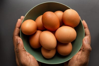person holding brown egg on green ceramic bowl egg teams background