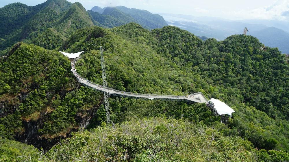 white bridge over green mountains during daytime
