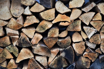 brown and black firewood on black round fire pit