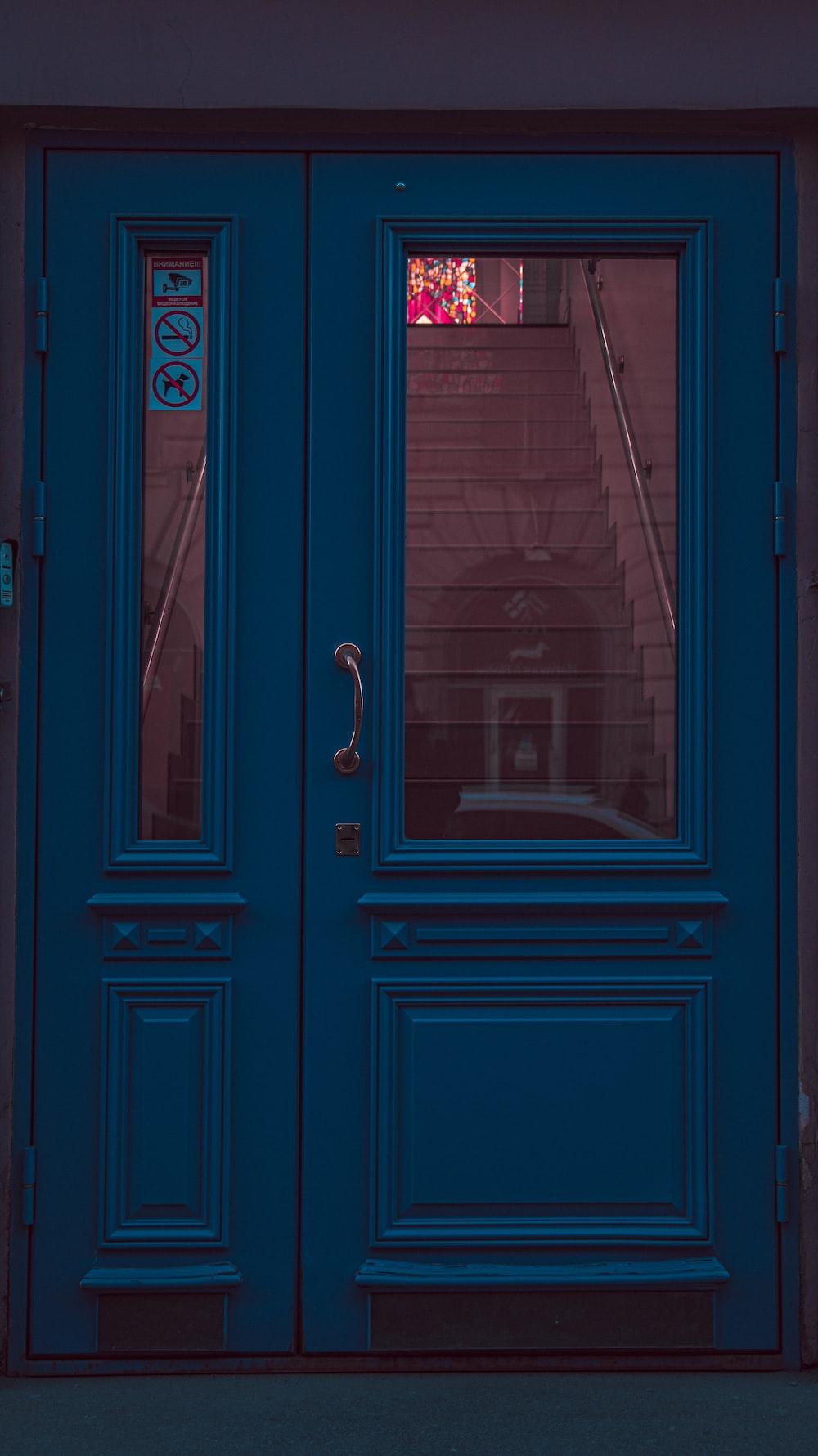 blue wooden door with black steel door lever