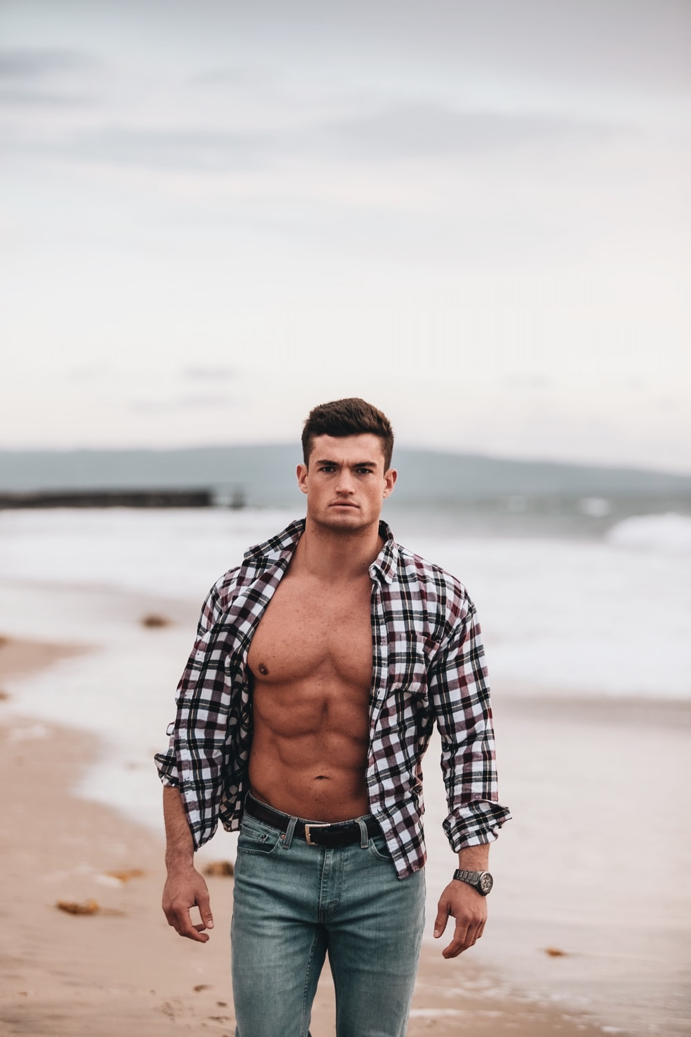 man in black and white plaid dress shirt standing on beach during daytime