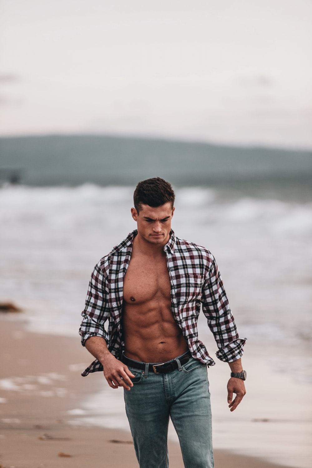 man in black and white checkered dress shirt and blue denim jeans standing on shore during
