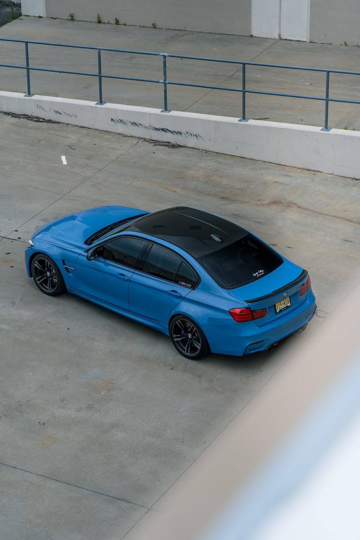 blue sedan parked on gray concrete floor
