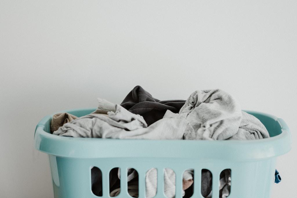 white textile on blue plastic laundry basket