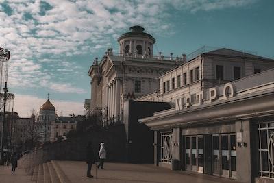 people walking on sidewalk near brown concrete building during daytime neoclassical teams background