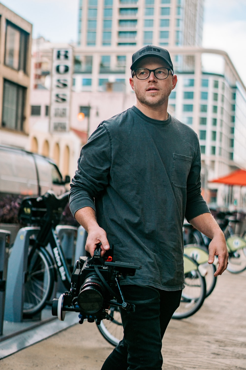 man in black long sleeve shirt and black sunglasses standing beside black bicycle during daytime