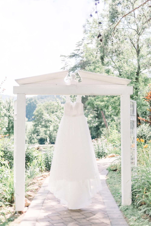 white wedding gown on white wooden frame