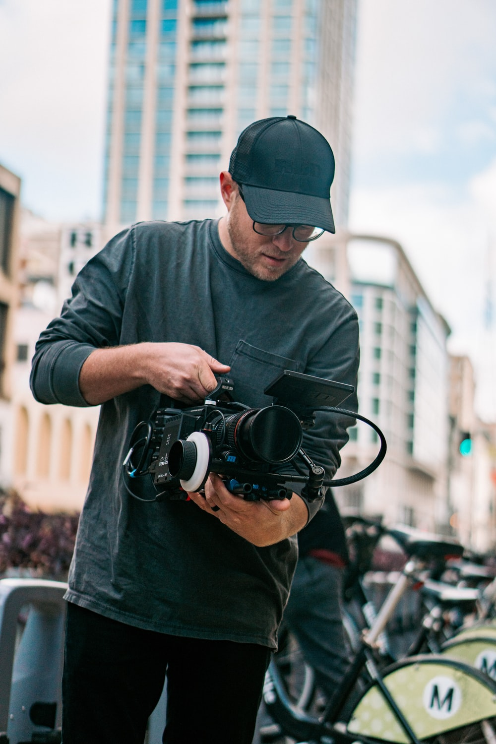 man in black long sleeve shirt holding black dslr camera