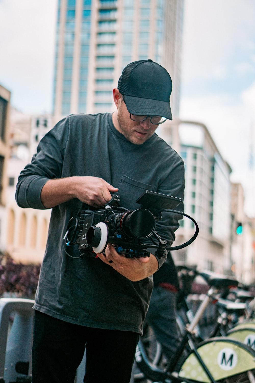 man in black long sleeve shirt holding black dslr camera