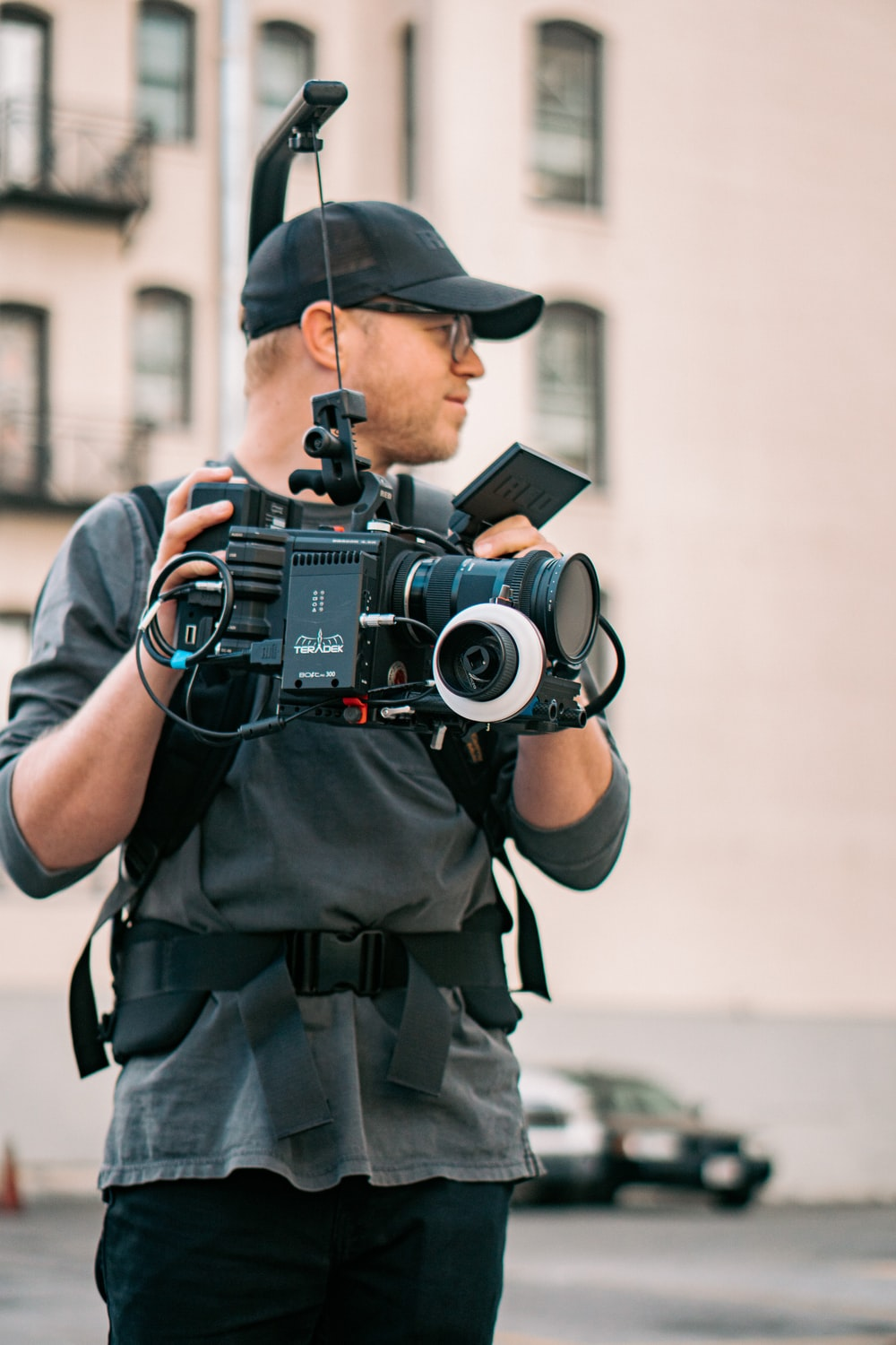 man in black and gray camouflage uniform holding black dslr camera